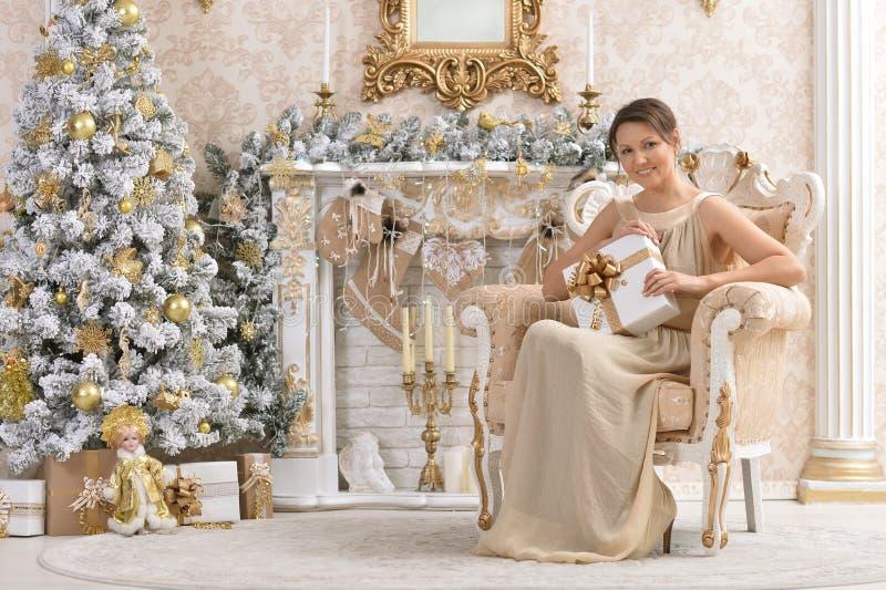 Härligt kvinnasammanträde i stol med julklapp nära tr royaltyfri foto
