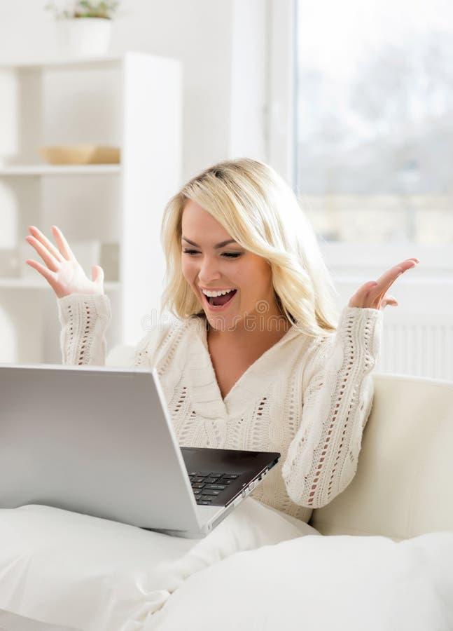 Härligt kvinnasammanträde på soffan genom att använda en bärbar dator royaltyfria foton