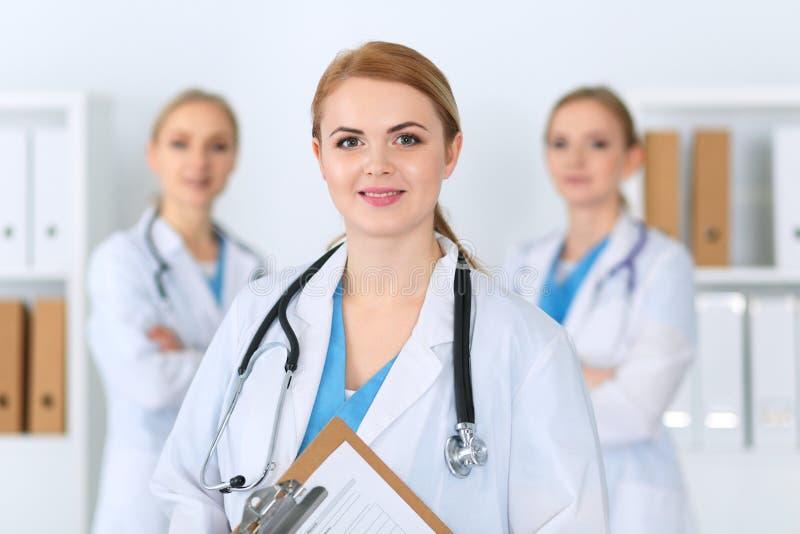 Härligt kvinnligt anseende för medicinsk doktor på sjukhuset framme av den medicinska gruppen Läkaren är klar att hjälpa patiente royaltyfri fotografi
