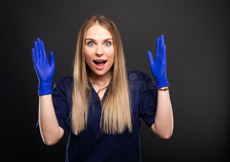 Härligt kvinnligt bära för tandläkare skurar att se lyckligt royaltyfria bilder