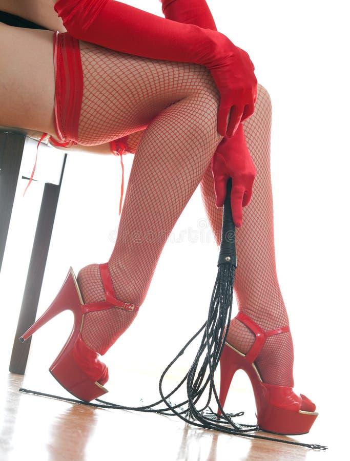 Kvinnligt lägger benen på ryggen och piskar royaltyfri fotografi