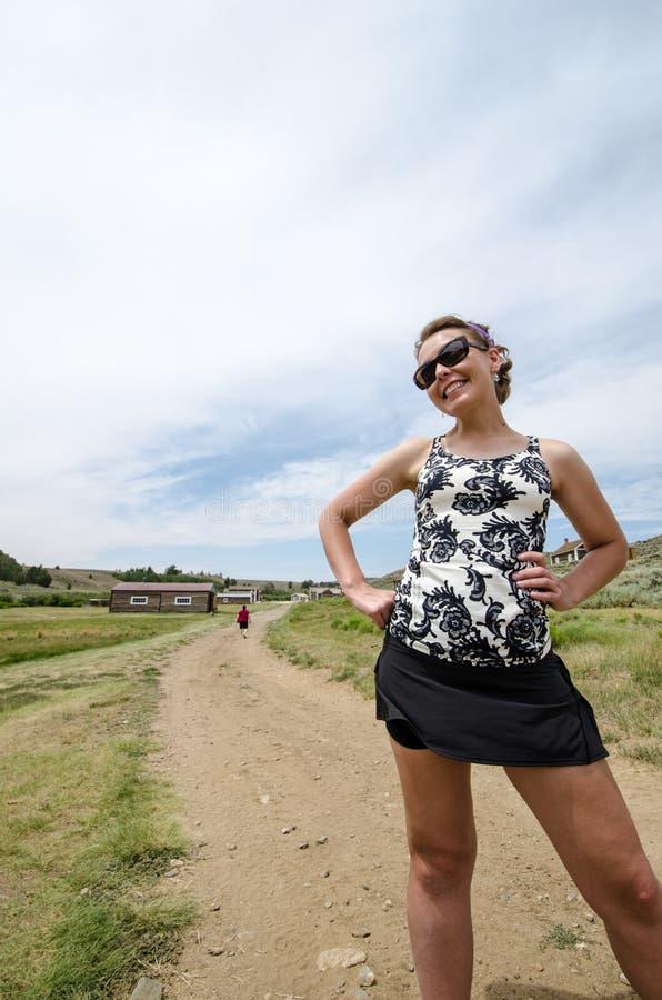 Härligt kvinnligt står och poserar vid en grusväg i Wyoming på S arkivfoto