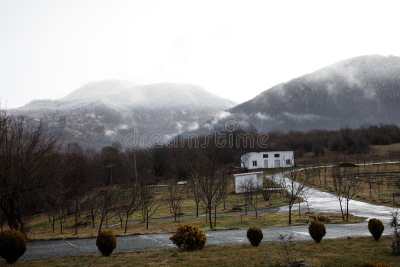 Härligt landskap av berg och skogen med bybyggnad eller det gamla övergav förstörda tegelstenhuset Dimmig skog och gammal buildi arkivbilder