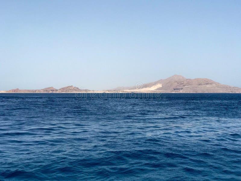 Härligt landskap av det blåa salta havet och de avlägsna höga bergen arkivbild
