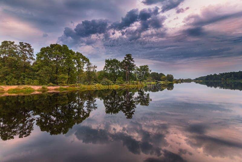 Härligt landskap av sjön på den färgrika solnedgången royaltyfria foton