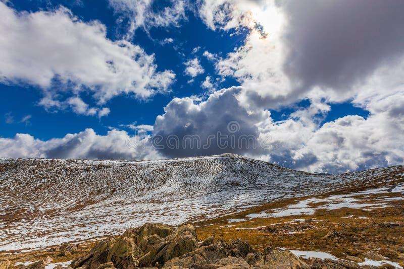 Härligt landskap av snö-täckte berg och fluffiga moln royaltyfri bild