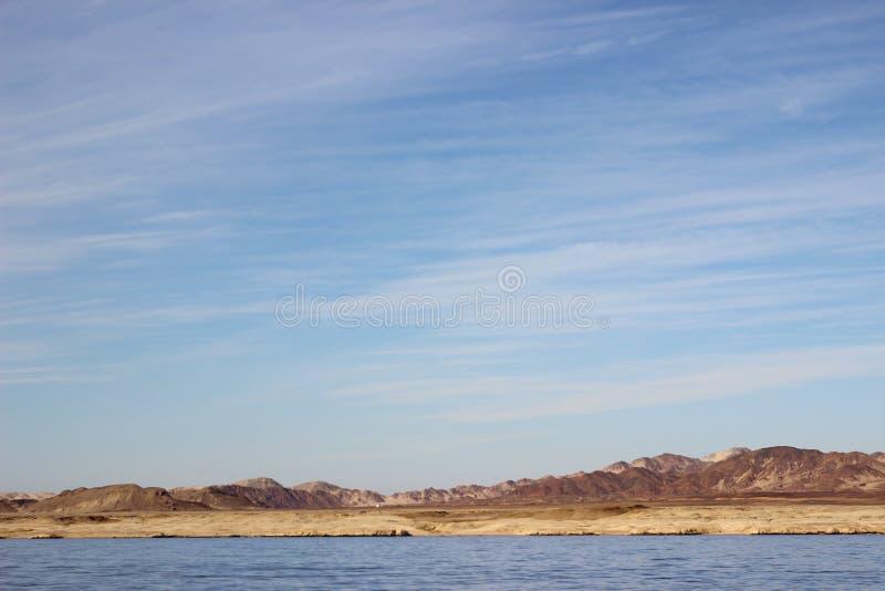 Härligt landskap Egyptiska berg och Röda havet Ljus fördunklar i den blåa himlen royaltyfria foton