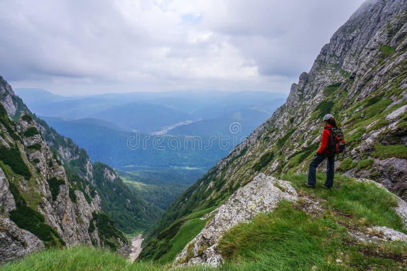 Härligt landskap i bergen och kvinnaklättraren som beundrar sikten fotografering för bildbyråer