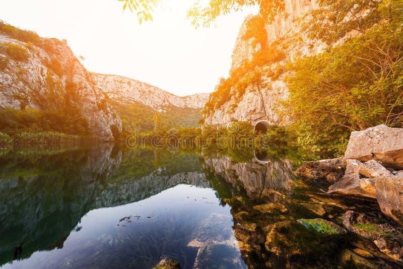 Härligt landskap, kanjon av den Cetina floden med reflexion i kristallklart vatten på solnedgången, Omis, Kroatien royaltyfria foton