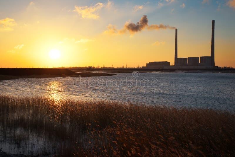 Härligt landskap med den termisk kraftverket, sjön och solnedgång arkivfoto