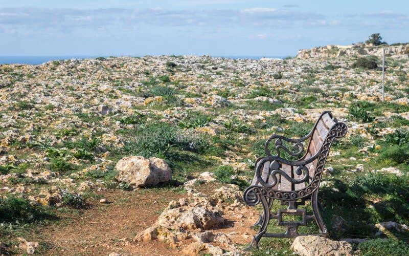 Härligt landskap med en gammal ensam bank på Dingli klippor i ett fält av stenar fotografering för bildbyråer