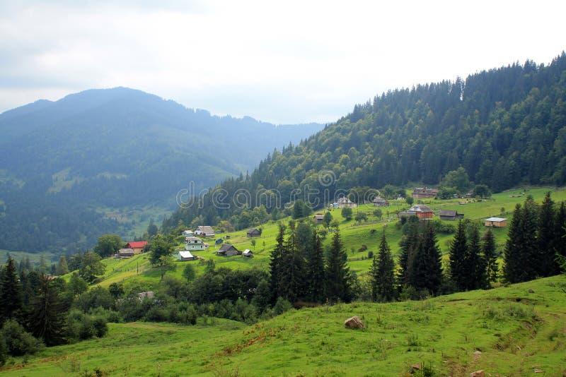 Härligt landskap med sikt till byn på backen och mountaien royaltyfri foto