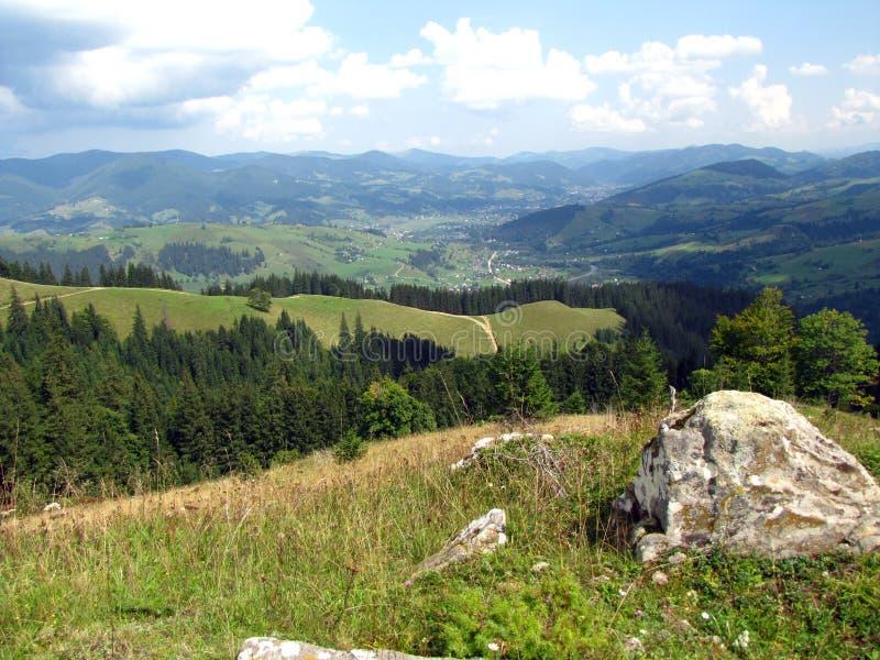 Härligt landskap med sikt till byn på dalen och berg i avstånd fotografering för bildbyråer