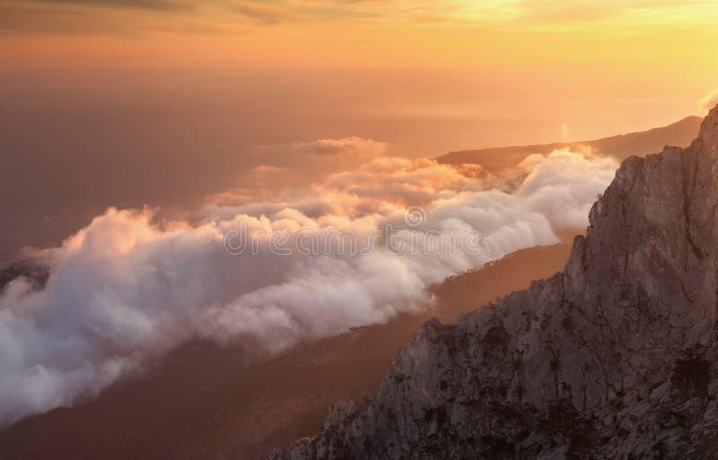 Härligt landskap på berget med låga moln på solnedgången arkivbild
