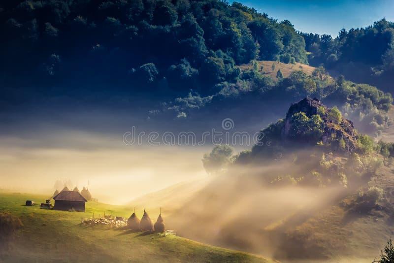 Härligt lantligt berglandskap i morgonljuset med dimma, gamla hus och höstackar arkivbild