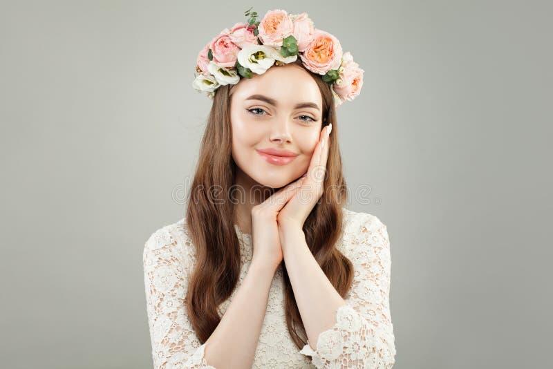 Härligt le koppla av för kvinna Nätt modellframsida med klar hud, den långa lockiga frisyren och blommor royaltyfri bild