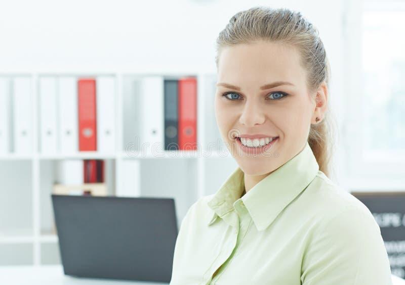 Härligt le sammanträde för affärskvinna på den halva vänden för kontorsarbetsplats som in camera ser ståenden royaltyfri bild
