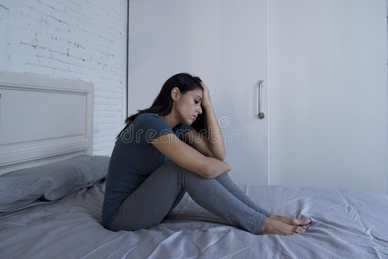 Härligt ledset och deprimerat latinskt kvinnasammanträde på säng hemmastatt f royaltyfria foton