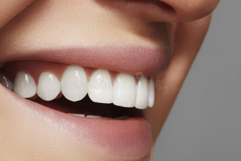 Härligt leende med blekmedeltänder Tand- foto Makrocloseup av den perfekta kvinnliga munnen, lipscarerutine royaltyfria bilder