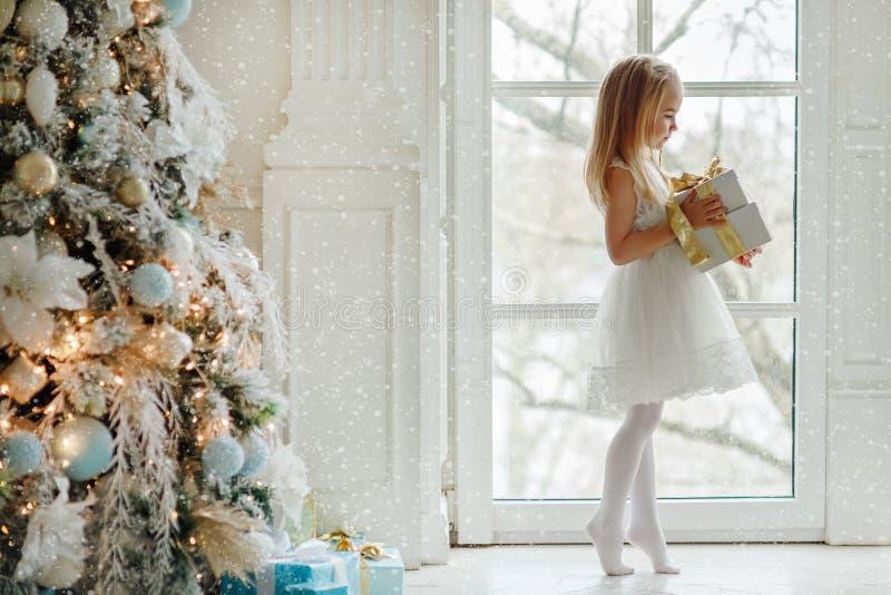 Härligt liten flickaanseende på tåspetsarna på det stora fönstret royaltyfri foto