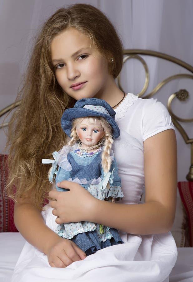 Härligt liten flickasammanträde på en säng och kramar henne behandla som ett barn - dockan royaltyfri fotografi