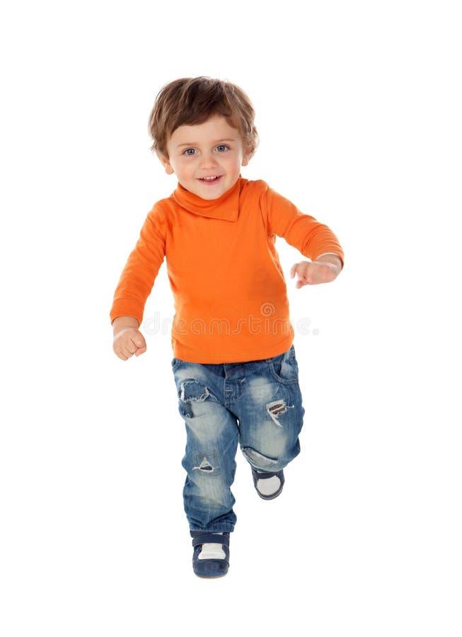 Härligt litet barn två år gammal bärande jeans och orange je arkivbild
