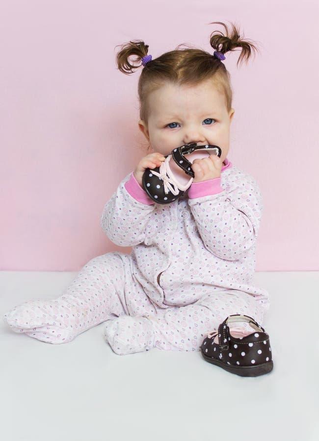 Härligt litet en begynnande flicka sitter och spelar med children& x27; s-skor royaltyfri fotografi