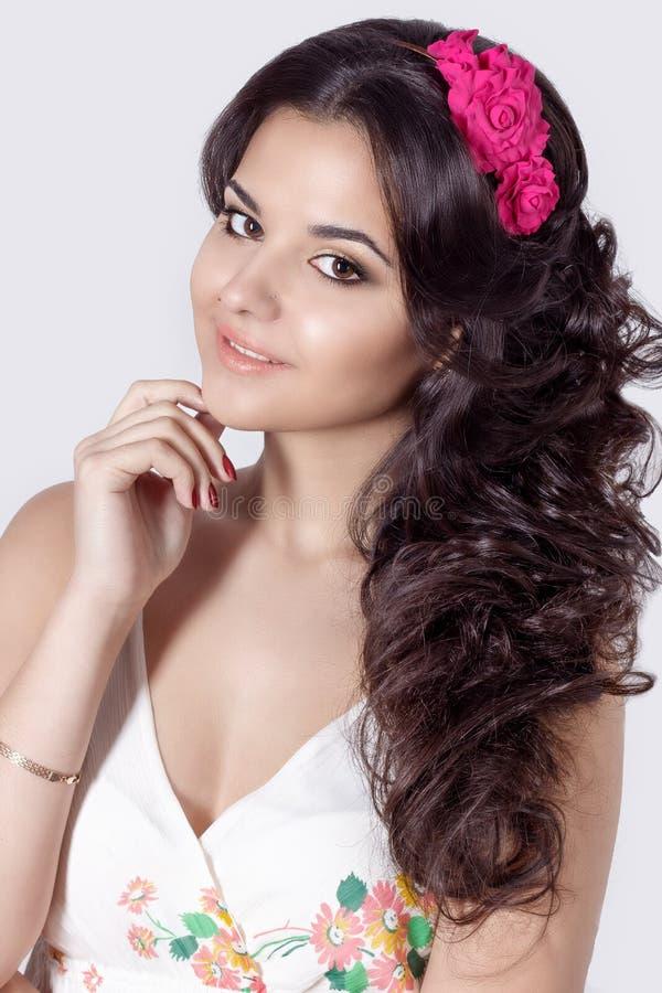 Härligt ljust le en mjuk söt flicka med långt svart lockigt hår med en krans av blommor i hår i sommarvitsundress royaltyfria bilder