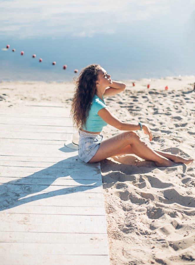 Härligt lockigt flickasammanträde för fred och för avkoppling på stranden Modell i profil semesterlynnekvinna som bort tänker och fotografering för bildbyråer