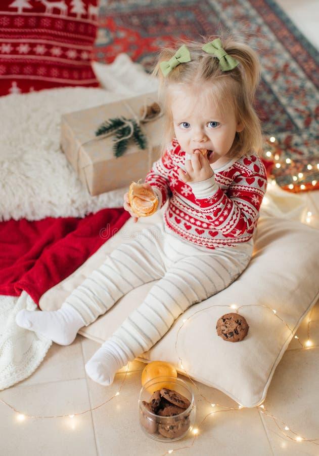 Härligt lyckligt behandla som ett barn flickan nära julgranen arkivfoto
