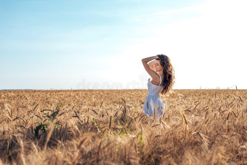 Härligt lyckligt kvinnafält, solig eftermiddag, vit klänning Brunetthår, garvad hud, begrepp av att tycka om naturen Lyckligt royaltyfri fotografi