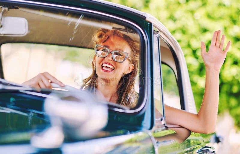Härligt lyckligt kvinnasammanträde i en bil arkivfoto