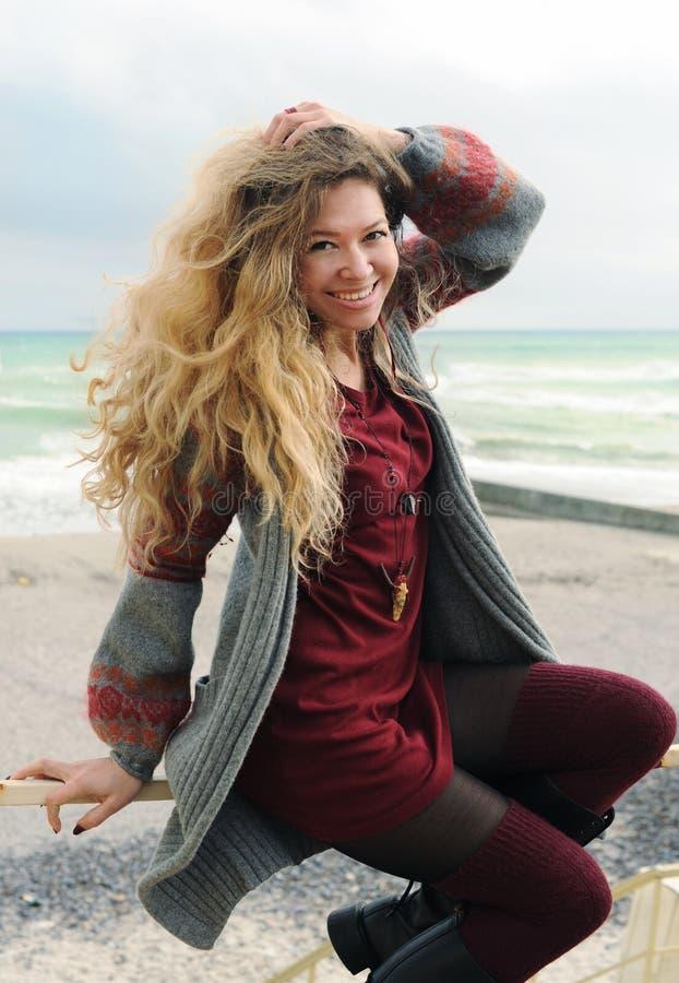 Härligt lyckligt le kvinnaståendesammanträde på en trappräcke mot hösthavet, långa hår, kortslutningsmodemörker - röd klänning oc arkivbilder