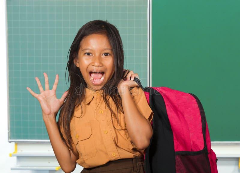Härligt lyckligt och upphetsat kvinnligt barn i påse för student för skolalikformig som bärande ler gladlynt anseende på klassrum royaltyfri fotografi