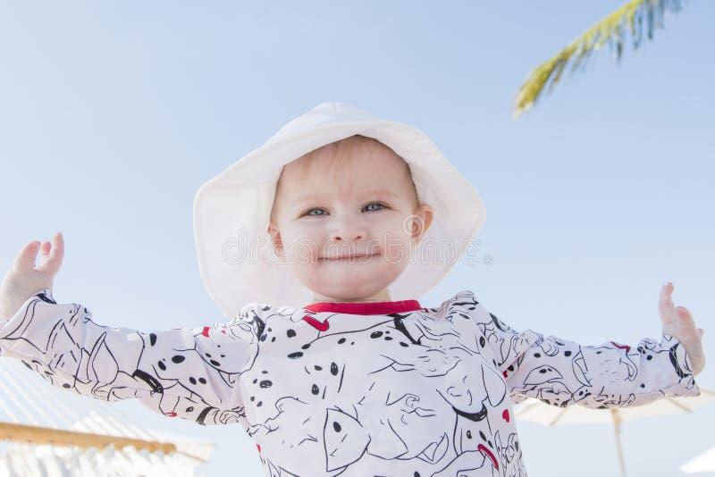 Härligt lyckligt uttrycksfullt blont flickalitet barn i en hängmatta på stranden arkivfoton