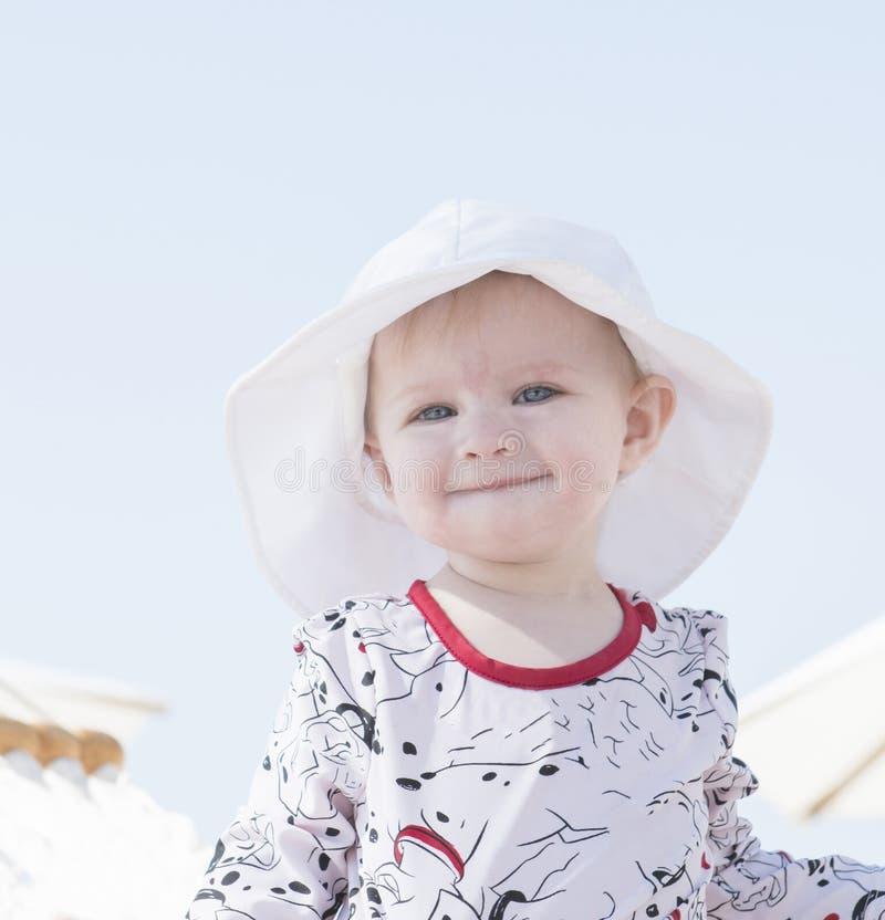Härligt lyckligt uttrycksfullt blont flickalitet barn i hängmatta på stranden royaltyfria bilder