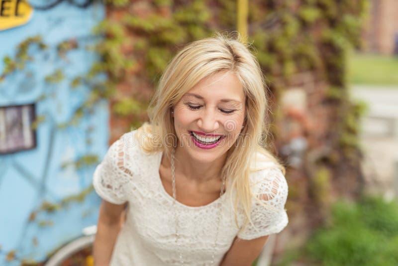 Härligt medelålderst blont skratta för kvinna royaltyfri foto
