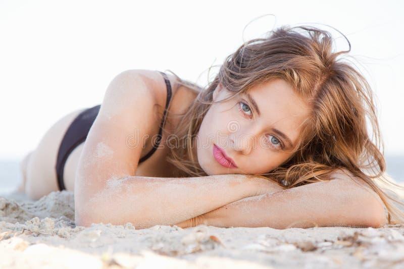 Härligt model ligga i sand royaltyfria foton