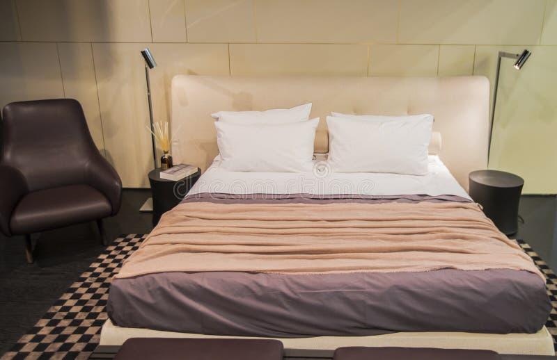 Härligt modernt antikt märkes- sovrum i pastellfärgade färger, med läderfåtöljen och golvlampor arkivfoto