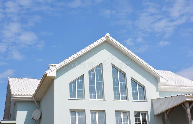 Härligt modernt hus med vita väggar, vita taktegelplattor och stora panorama- hem- loftfönster arkivbild