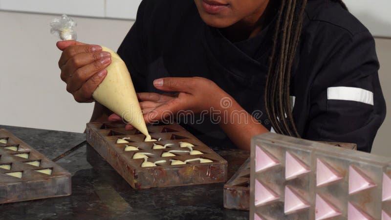 Härligt moget kvinnligt mer chocolatier le till kameran, medan arbeta royaltyfri fotografi