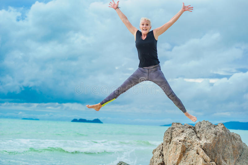 Härligt mogna den åldriga kvinnan som gör yoga på en tropisk beac för öken arkivbild