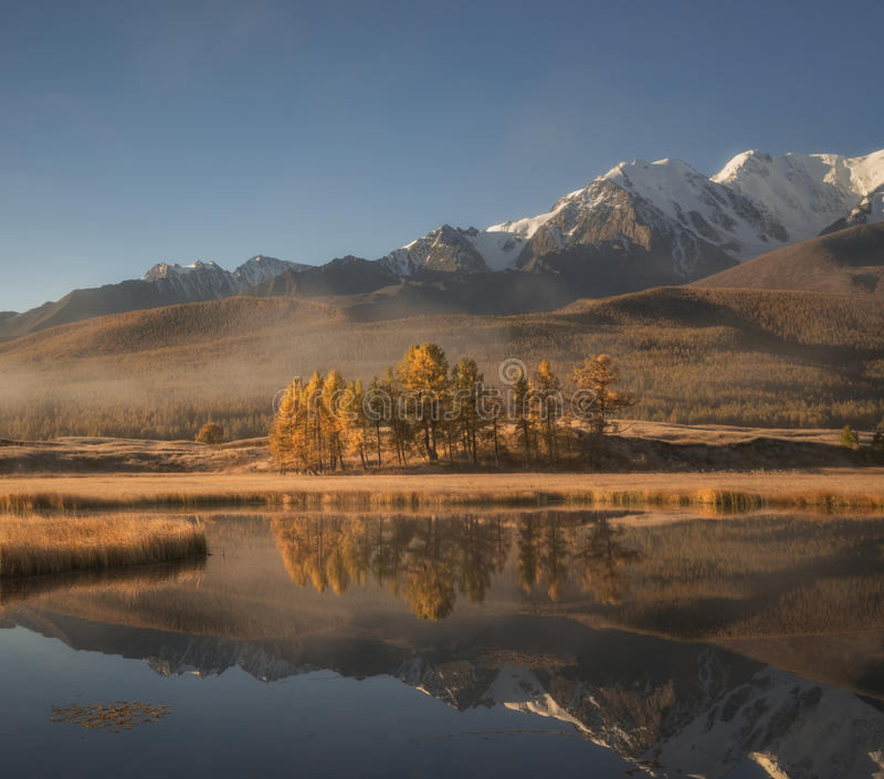 Härligt morgonhöstlandskap, bergsjö på bakgrunden av snöig berg fotografering för bildbyråer