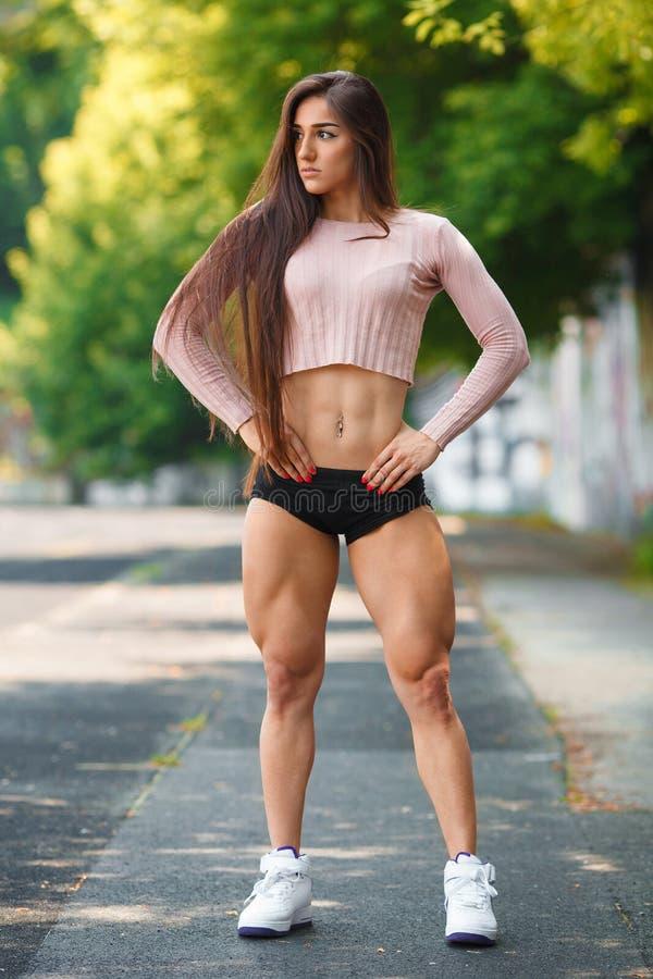 Härligt muskulöst posera för flicka som är utomhus- Sexig idrotts- kvinna med stora kvadrater royaltyfria foton