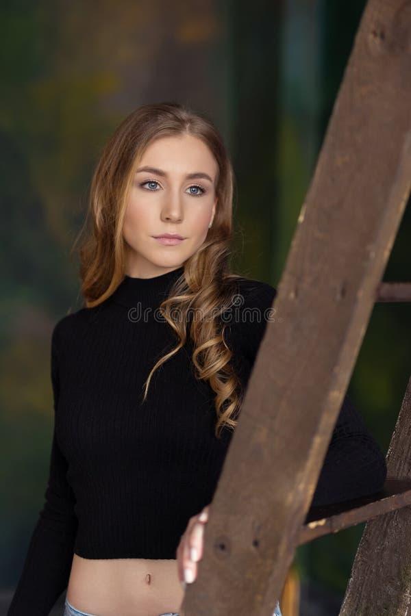 Härligt nätt anseende för ung kvinna som lutar på stegen I arkivbild