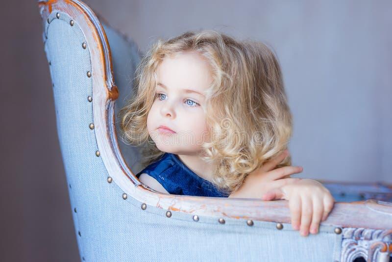 Härligt nätt litet barnflickasammanträde i fåtölj som bort ser royaltyfria foton