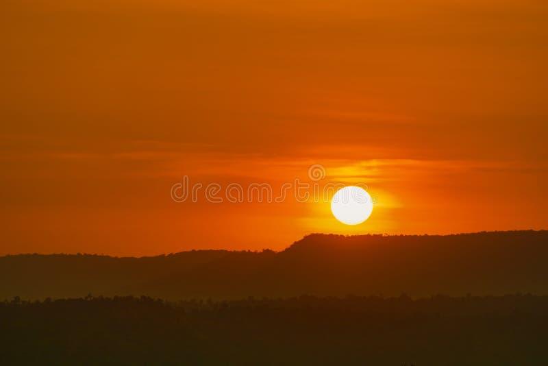 Härligt naturlandskap av berget med solnedgånghimmel och moln Landskap av berglagret på skymning med den stora runda solen naturl arkivbild