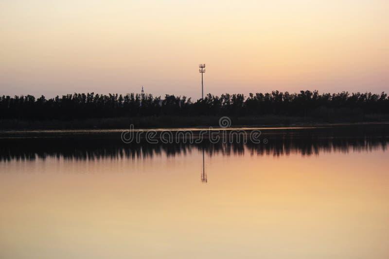 Härligt naturlandskap av vatten, träd och himmel skuggar i vattnet arkivfoton