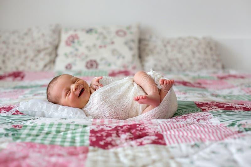 Härligt nyfött behandla som ett barn pojken och brett att le som slår in i sjal, lyien arkivfoton