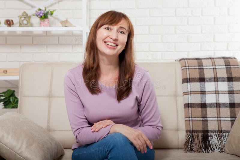 Härligt och gulligt le mellersta ålderkvinnasammanträde på soffan Hem- bakgrund Lyckligt klimakteriumbegrepp arkivbilder